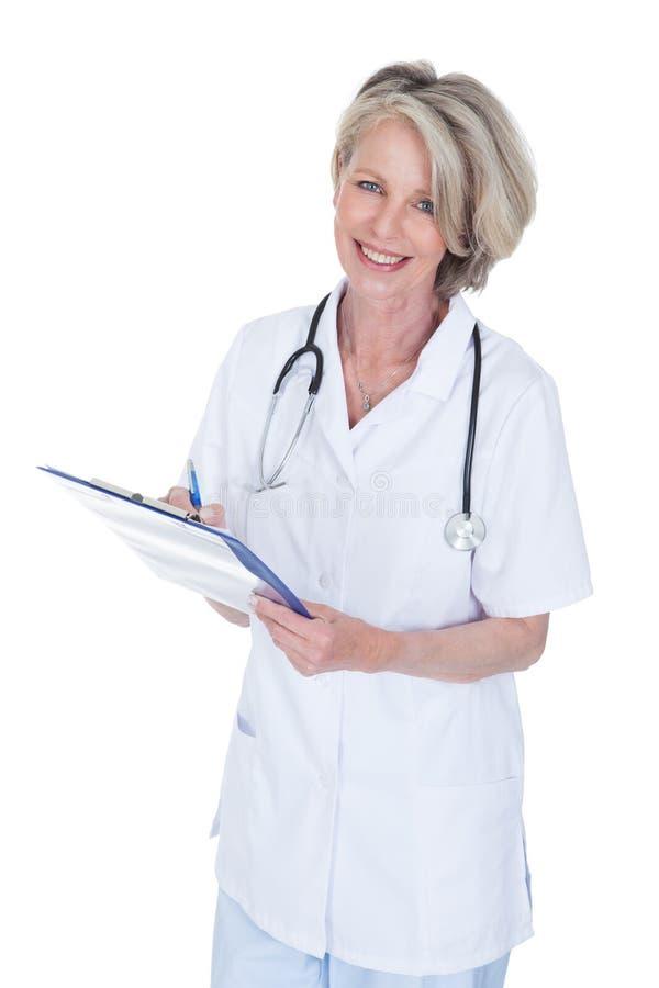 Écriture femelle mûre de docteur sur le presse-papiers photo stock