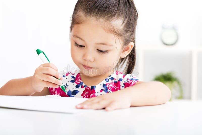 Écriture heureuse de petite fille dans le carnet images stock