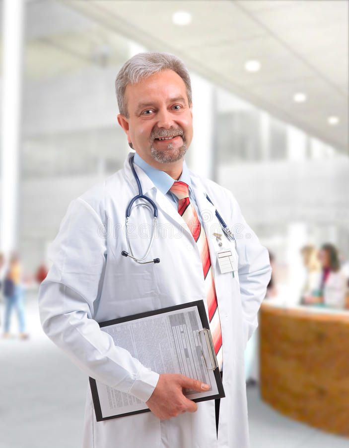 Écriture mûre de sourire heureuse de docteur sur la planchette image stock