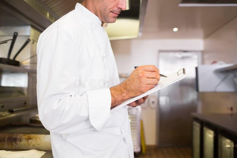 Écriture masculine concentrée de cuisinier sur le presse-papiers dans la cuisine photos libres de droits
