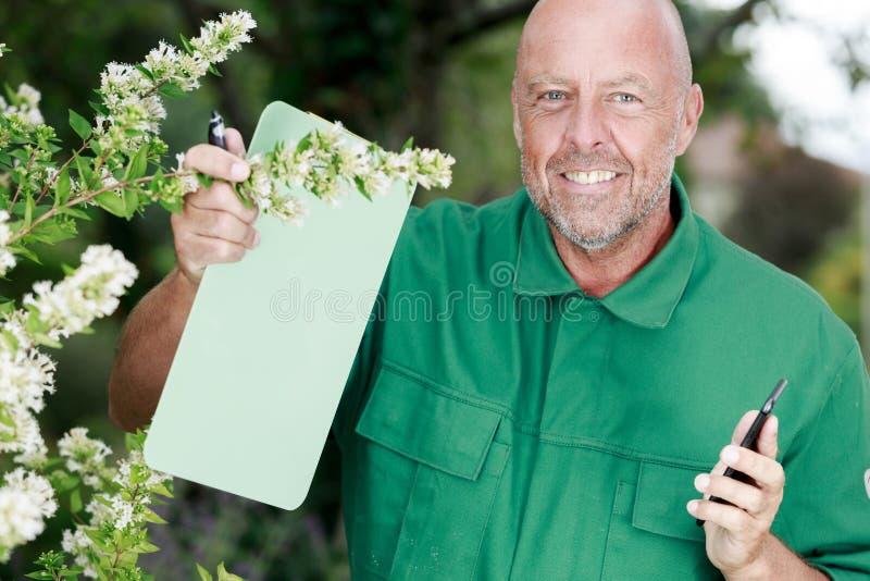 Écriture masculine de fleuriste sur le presse-papiers au fleuriste photo libre de droits