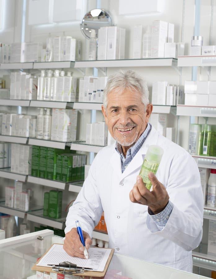 Écriture masculine de Holding Product While de pharmacien sur le presse-papiers photographie stock