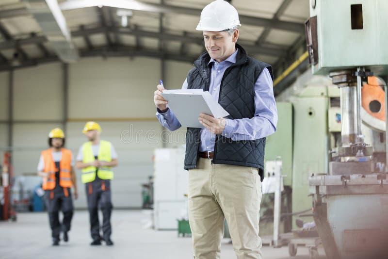 Écriture masculine mûre d'inspecteur sur le presse-papiers tandis que travailleurs à l'arrière-plan à l'usine image stock