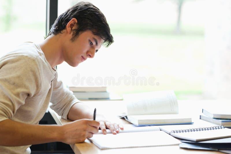 Écriture sérieuse d'étudiant mâle images stock