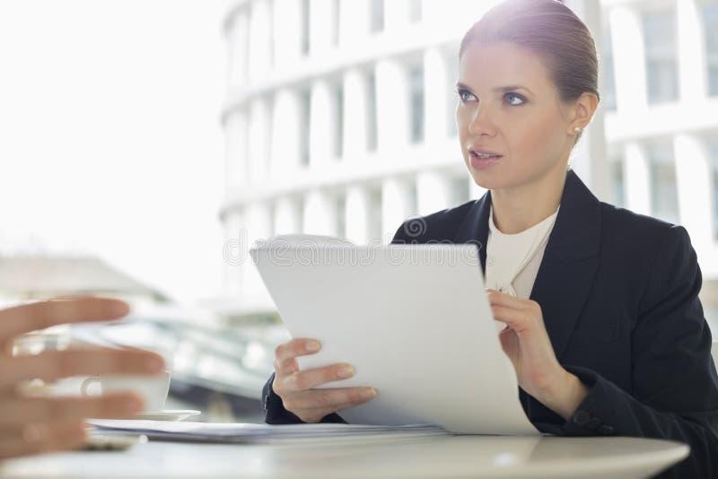 Écritures de discussion de femme d'affaires avec le collègue dans le cafétéria de bureau images stock
