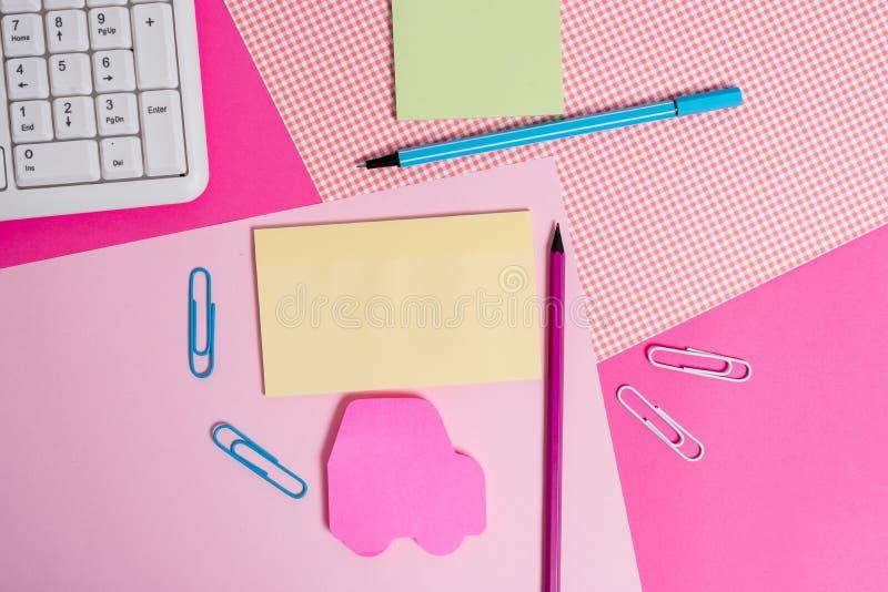 Écrivant des équipements et des substances d'ordinateur plus le papier de notation placé sur un contexte coloré Stationnaire, feu photos stock