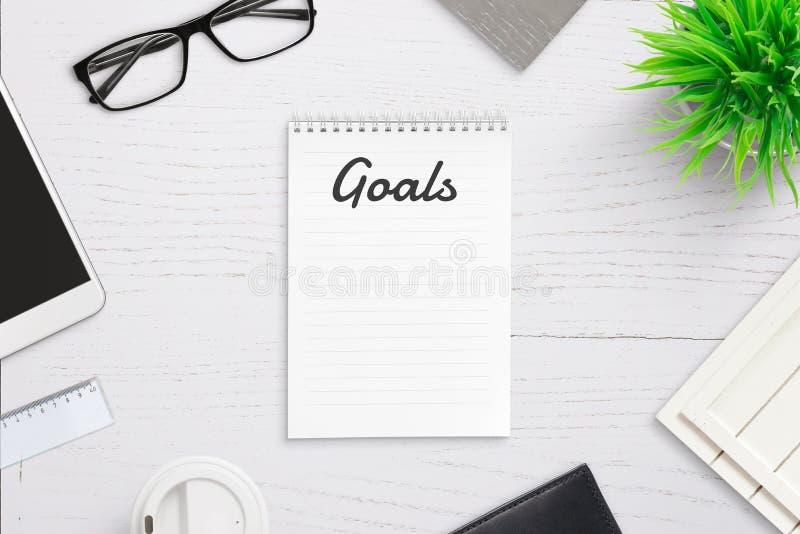 Écrivant les buts sur la page vide de bloc-notes avec des buts intitulent dans l'en-tête images stock