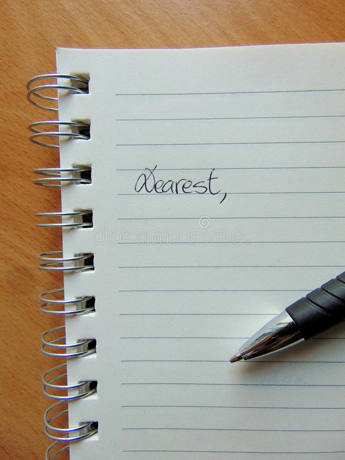 Écrivant une lettre sur le papier rayé commençant par cher, photo libre de droits