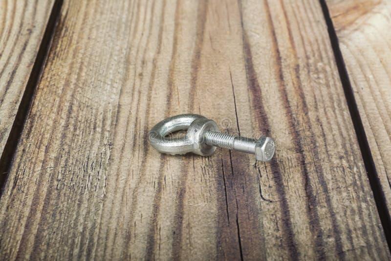 Écrou d'anneau avec le boulon, galvanisé sur le fond en bois images stock