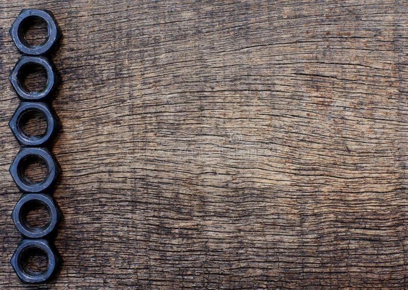 Écrou noir sur le fond en bois image libre de droits