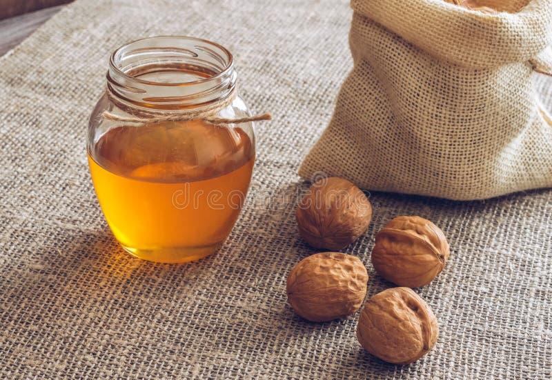 Écrous avec du miel Noix dans un sac de toile et miel dans un pot Table en bois avec la serviette de toile photos libres de droits