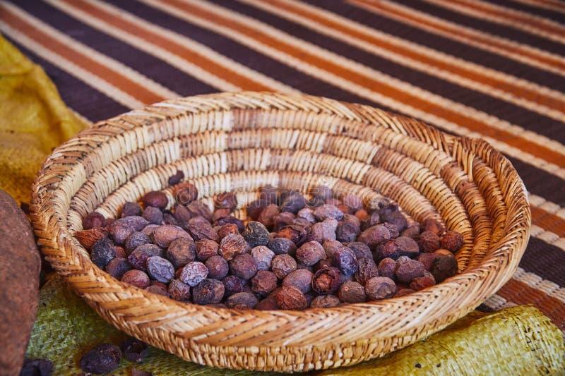 Écrous crus d'argan dans le panier en bois photo stock