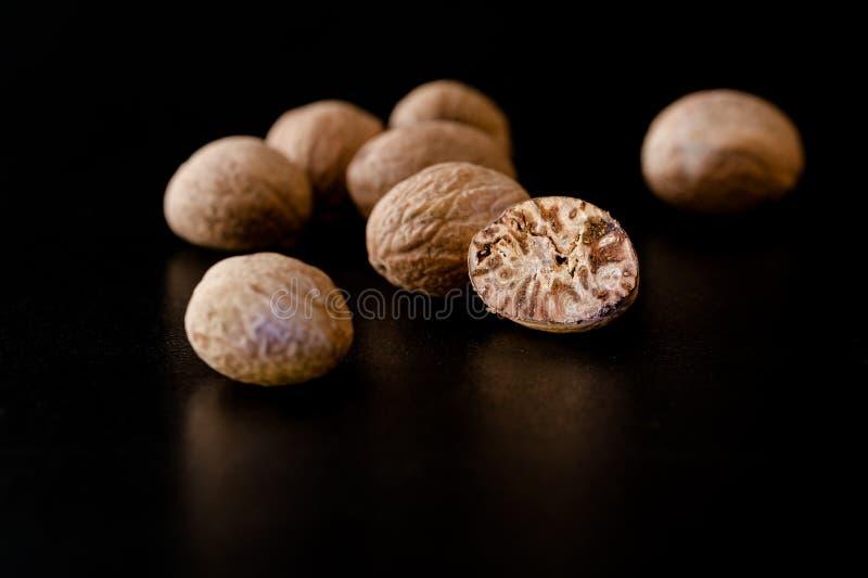 Écrous de noix de muscade et poudre entiers de noix de muscade à un arrière-plan noir photographie stock libre de droits