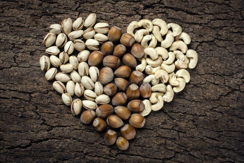Écrous en forme de coeur : noisettes, pistaches et anarcadiers images libres de droits