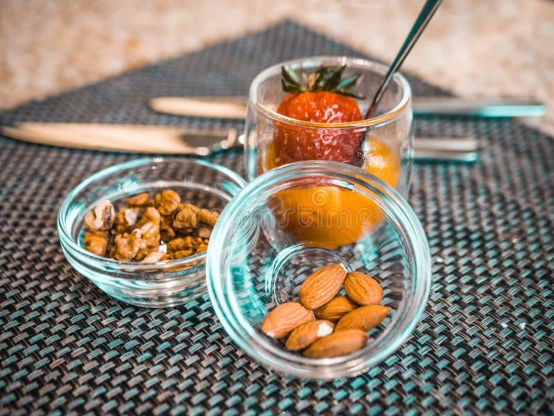 Écrous et fraises dans des bols en verre casse-croûte délicieux pour le petit déjeuner image stock