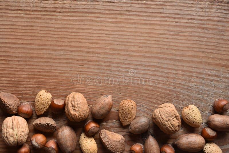 Écrous mélangés avec l'espace de copie sur le bois photos stock