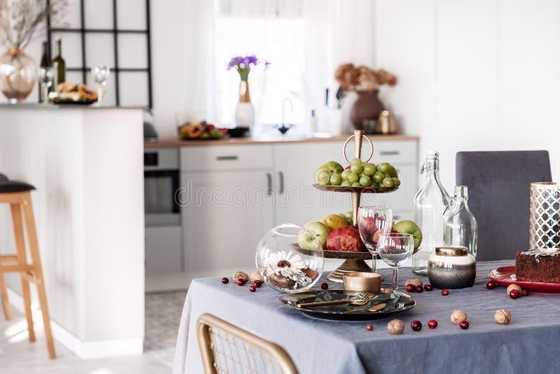Écrous, raisins et pommes sur la table de salle à manger avec les verres et le plat de vin avec la vaisselle photographie stock libre de droits