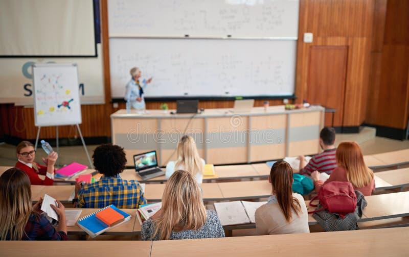 Éducation, école, étude et concept de personnes - groupe d'étudiants écoutant un conférencier photo libre de droits
