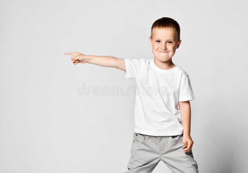 Éducation, école et concept de geste - petit garçon mignon indiquant le côté image libre de droits