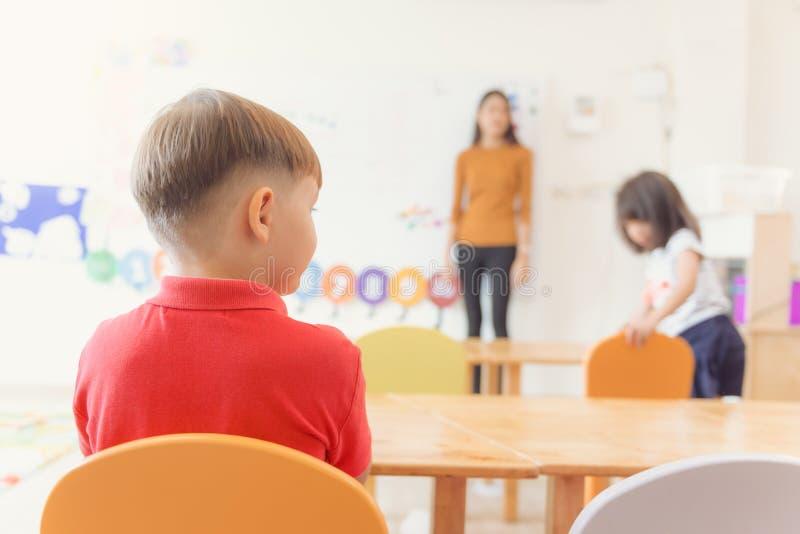 Éducation, école primaire, étude et concept de personnes - le groupe de l'école badine avec le professeur s'asseyant dans la sall photographie stock