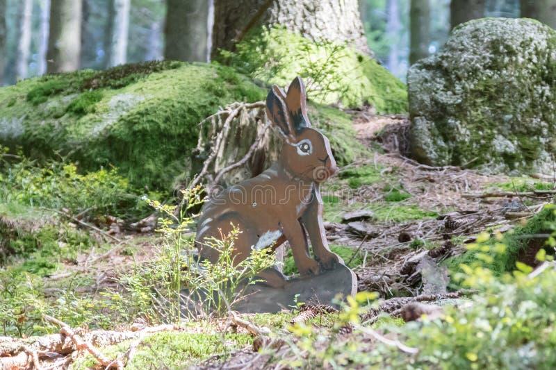 Éducation dans la forêt - lapin en bois attendant pour être repéré par images libres de droits