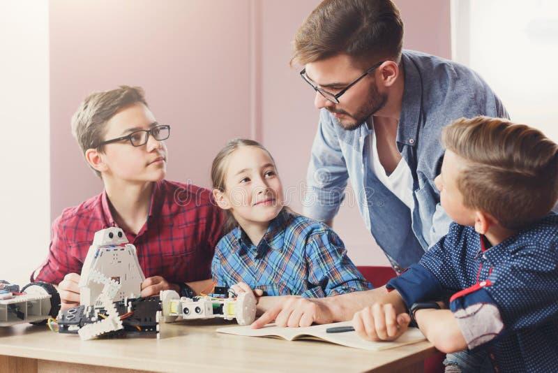 Éducation de TIGE Enfants créant des robots avec le professeur photographie stock libre de droits