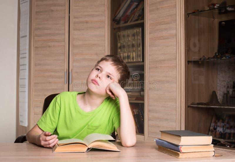 Éducation et concept d'école Garçon de l'adolescence lisant un livre à la maison image libre de droits