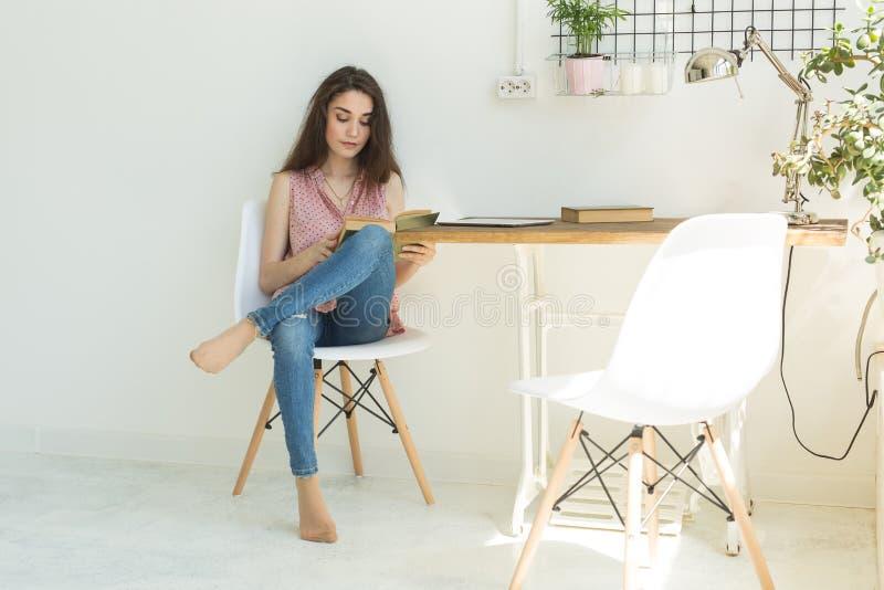 Éducation et concept de personnes - jeune femme s'asseyant sur la chaise avec le livre images libres de droits