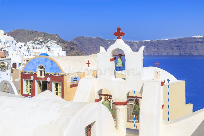 Église avec la Croix-Rouge et cloches vertes dans le village d'Oia, Santorini image stock