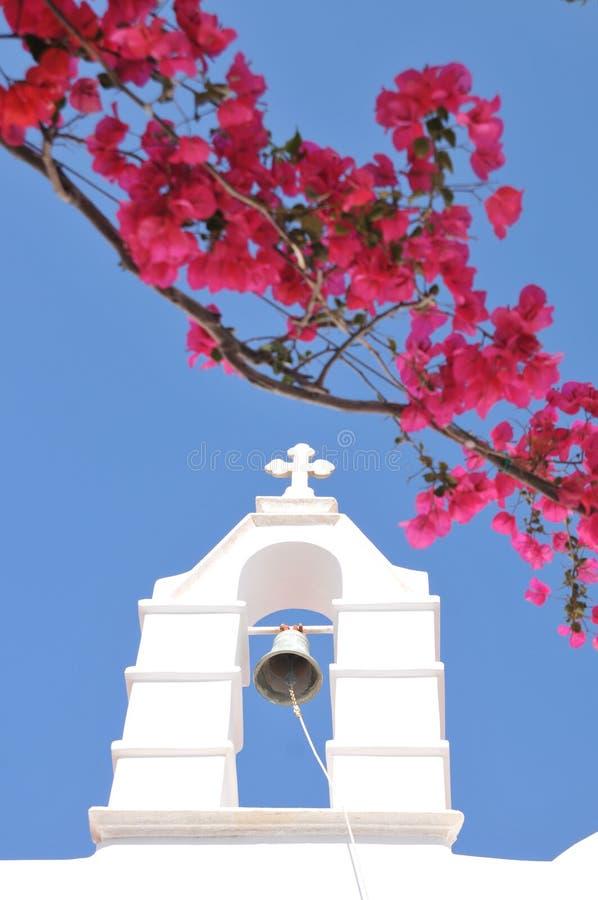 Église Bell et fleurs roses dans Mykonos, Grèce photographie stock