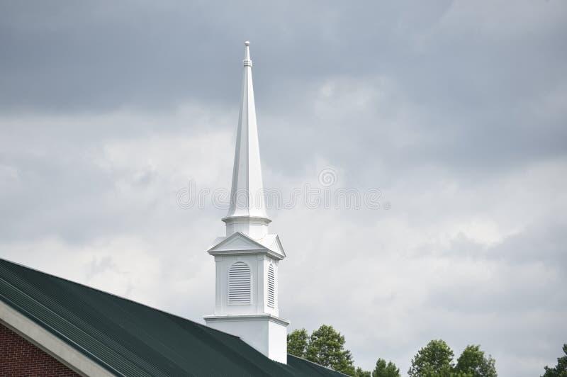 Église blanche Steeple avec des nuages de tempête images stock