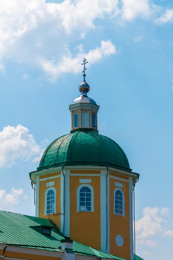 Église chrétienne orthodoxe jaune avec un Green Dome en été contre un ciel bleu avec les nuages blancs photos stock