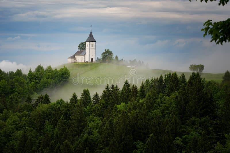 Église de Jamnik sur un flanc de coteau au printemps, temps brumeux au coucher du soleil en Slovénie, l'Europe Paysage de montagn images stock