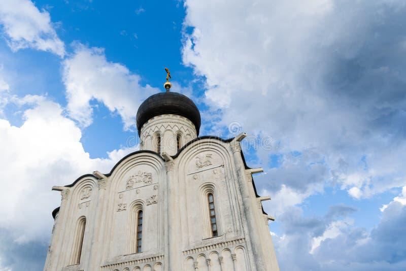 Église orthodoxe sur un pré vert avec les arbres et le ciel nuageux bleu photographie stock