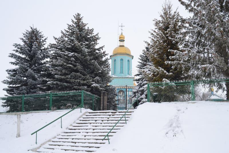 Église pendant l'hiver entre le sapin vert photographie stock libre de droits