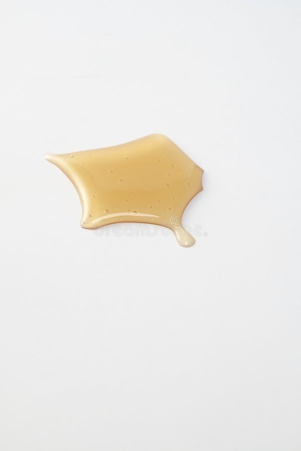 Égouttements doux de miel sur le blanc photographie stock libre de droits