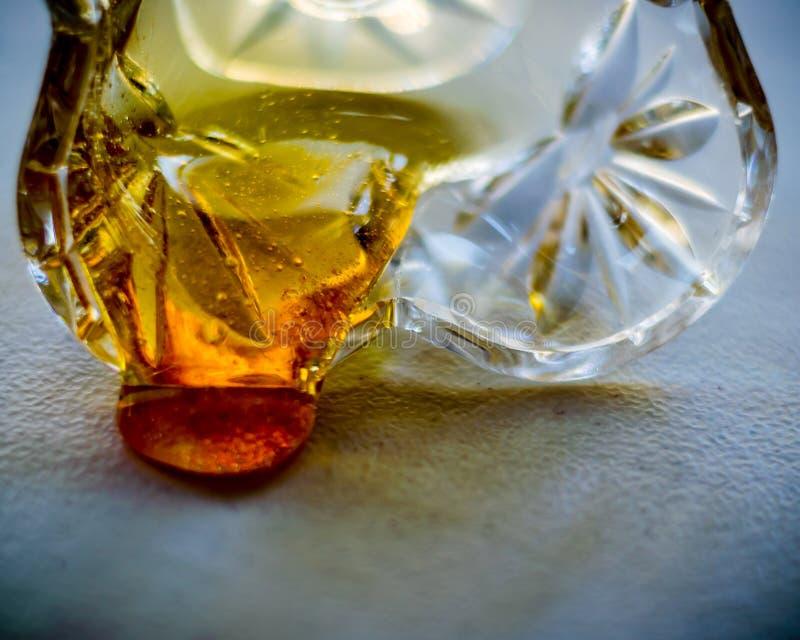 Égoutture de miel de bol en verre, plan rapproché, foyer discret et sélectif images stock