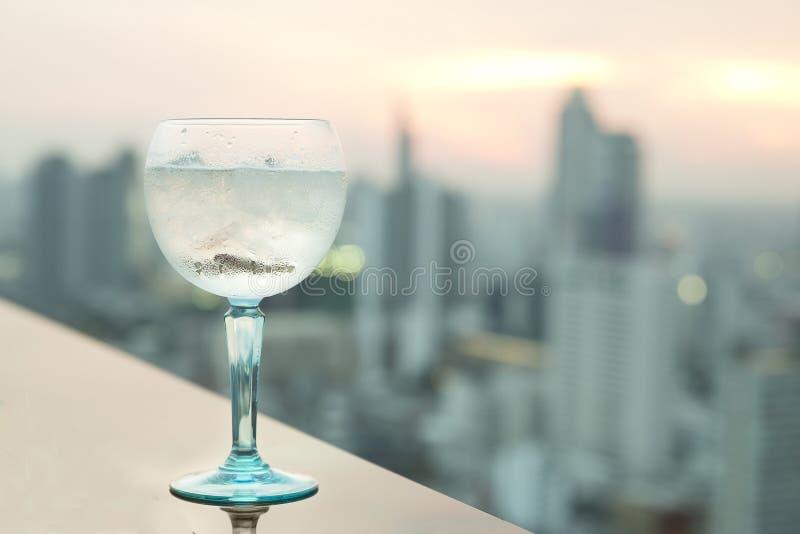 Égrenez le cocktail tonique sur la table dans la barre de dessus de toit photographie stock