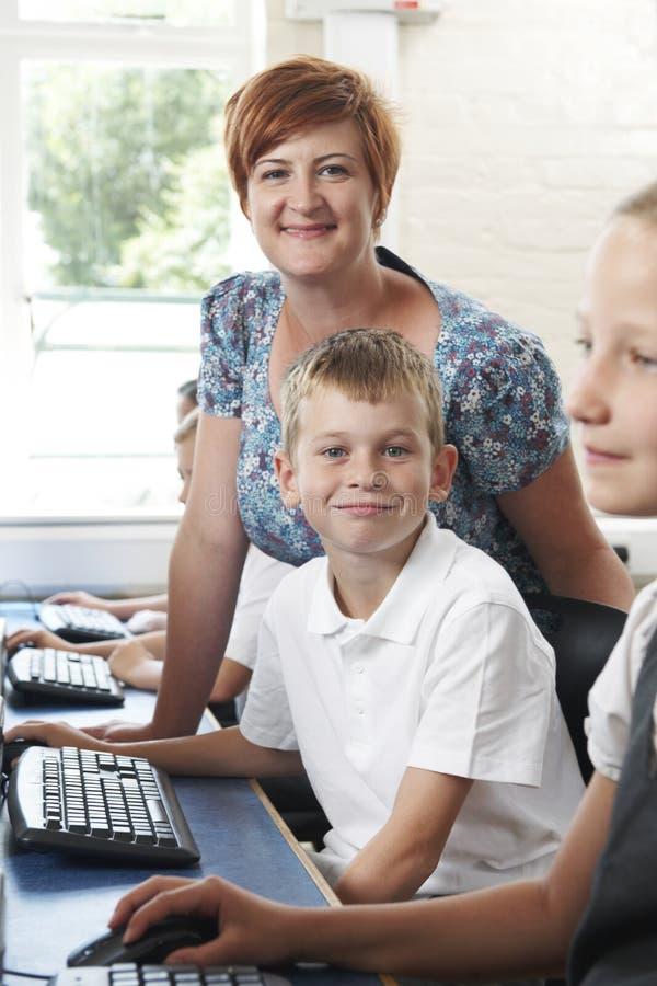 Élève élémentaire masculin dans la classe d'ordinateur avec le professeur images stock