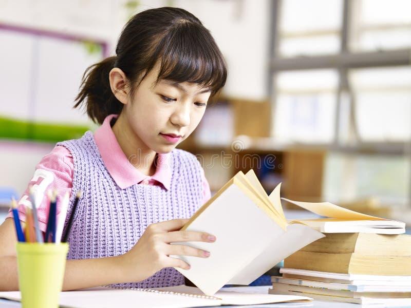 Élève asiatique lisant un livre dans la salle de classe images stock