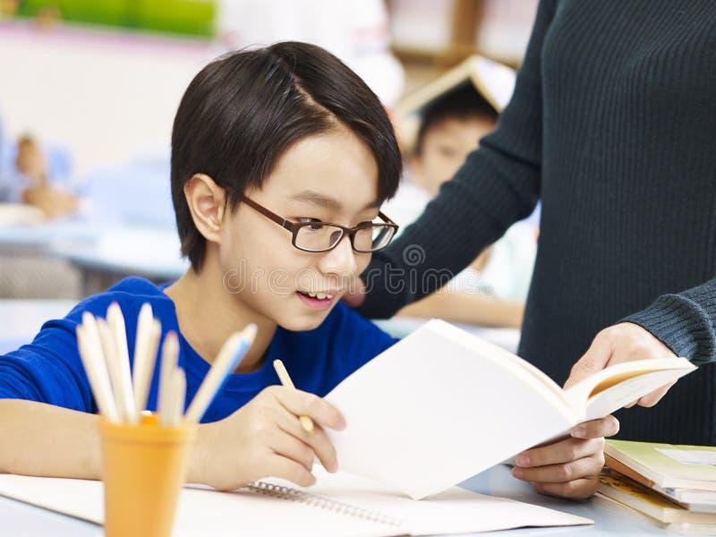 Élève asiatique obtenant l'aide du professeur images stock