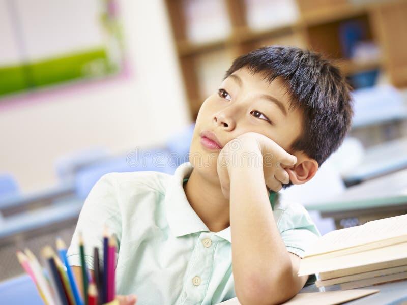 Élève asiatique rêvassant dans la salle de classe images stock