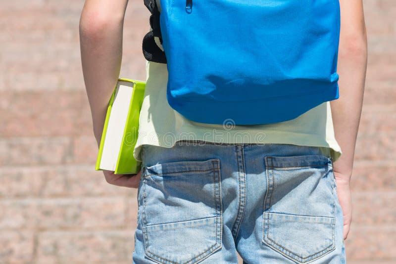 Élève avec un sac à dos sur le sien prises arrières un livre dans sa vue en gros plan de main par derrière photos stock