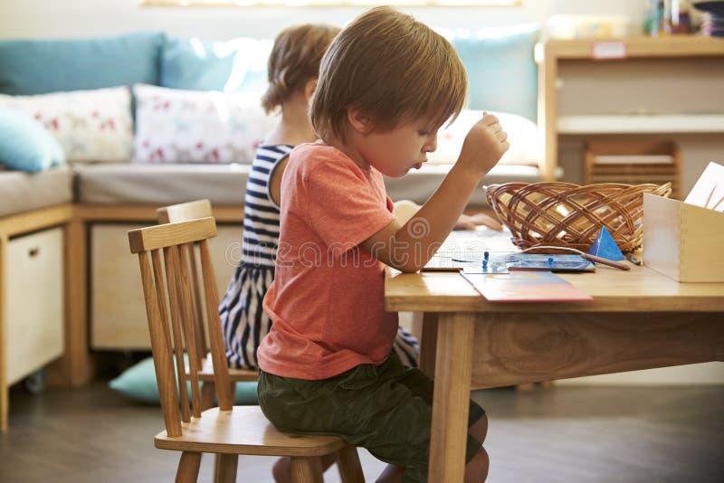 Élève de Montessori fonctionnant au bureau avec des formes en bois photo stock