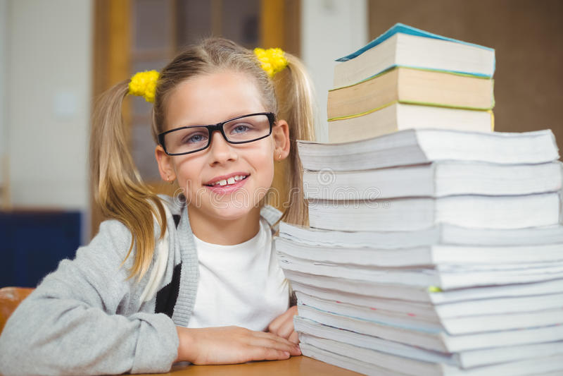 Élève de sourire à côté de la pile de livres sur son bureau photo stock