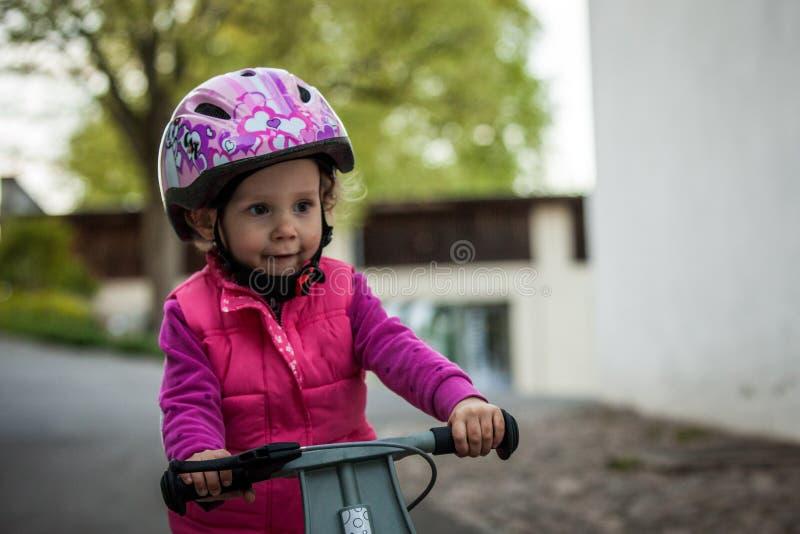 Élève du cours préparatoire apprenant à équilibrer sur la bicyclette dans le casque sûr photos stock