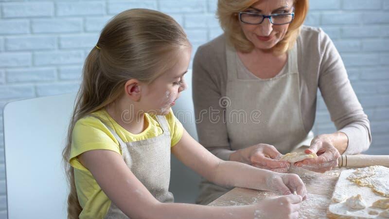 Élève du cours préparatoire assez féminin essayant de faire cuire la pâtisserie, aidant sa mamie dans la cuisine images stock