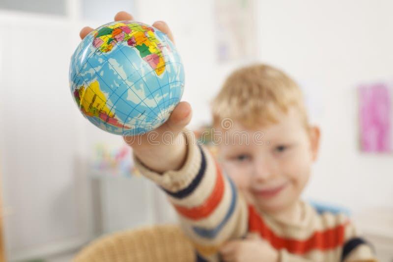 Élève du cours préparatoire avec le globe dans une main photos stock