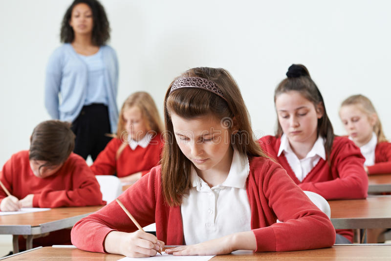 Élève femelle au bureau prenant l'examen d'école images libres de droits