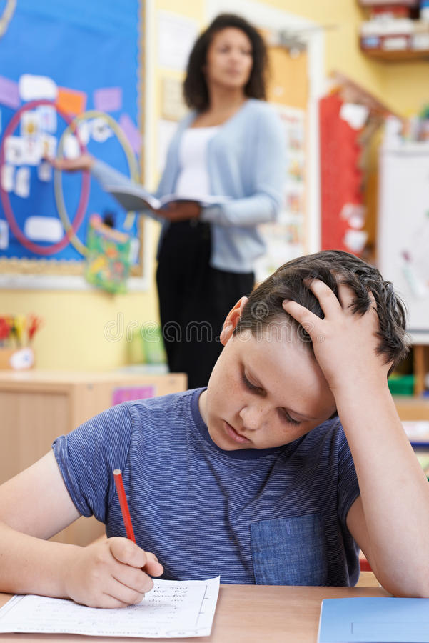 Élève masculin d'école primaire luttant dans la classe photos stock